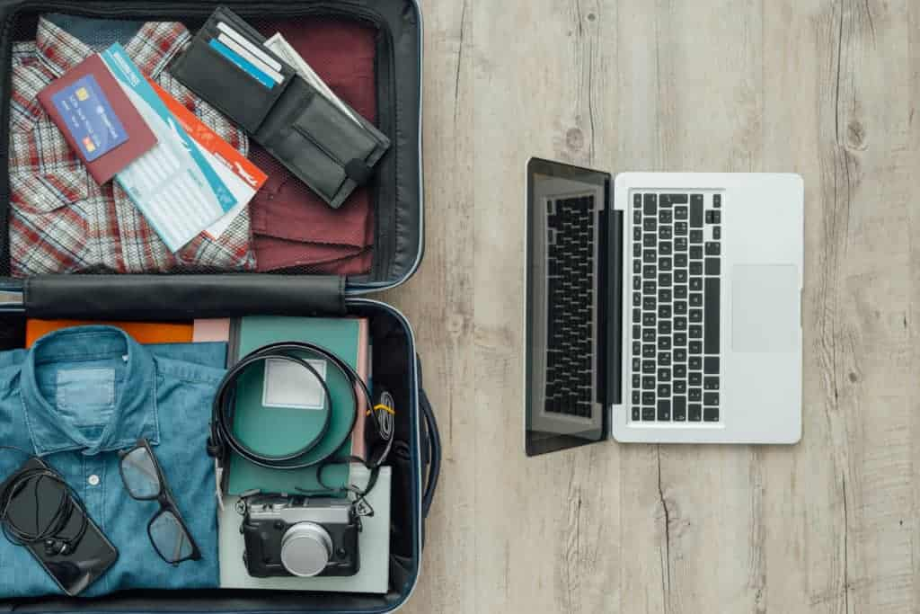 vacation travel reservation laptop and suitcase